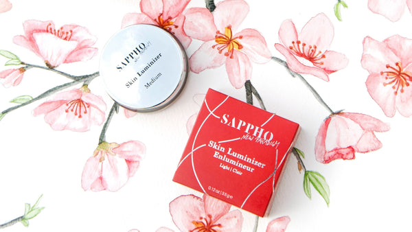 Vegan SKin Luminizer pot and red box packaging scattered over cherry blossom painting