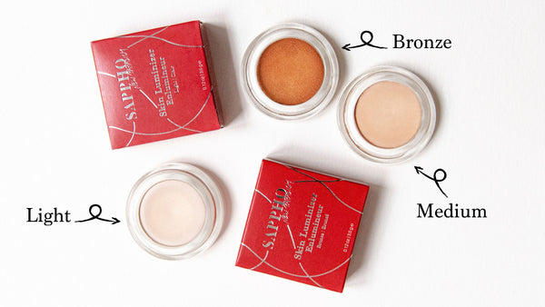 Three open skin luminizer pots showing shades Light, Medium & Bronze for all skin tones and two red recyclable box packaging