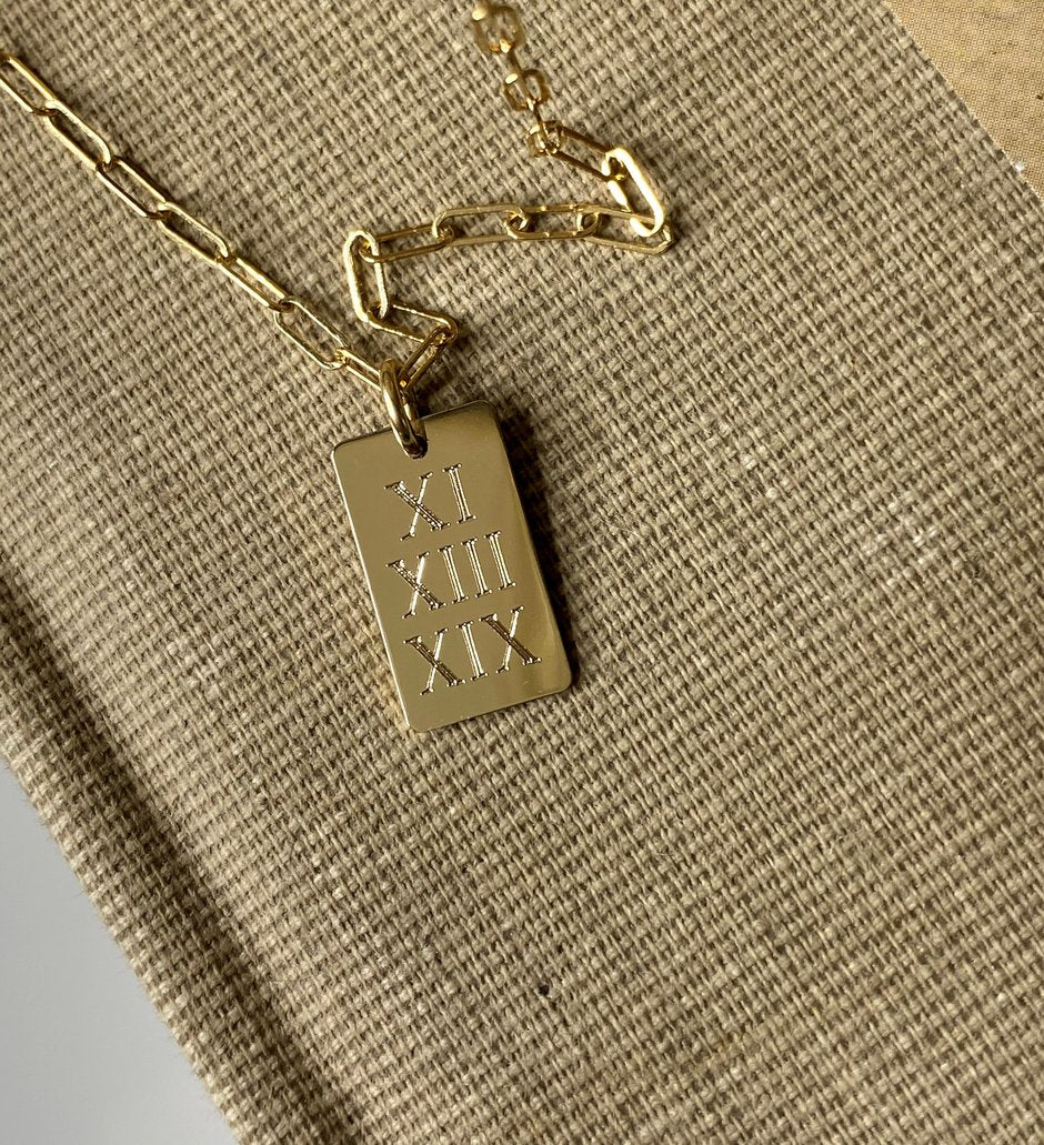 http://www.gemsinvogue.com/collections/necklaces/products/large-bar-anniversary-date-roman-numeral-engraved-nameplate-necklace?variant=1658537475