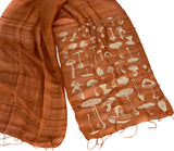 Ivory-cream ink on cinnamon silk scarf.