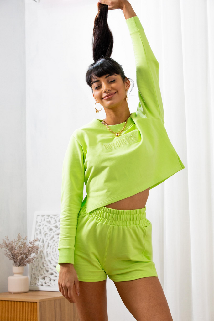 Model poses holding her ponytail up in the air, eyes shut wearing doyoueven activewear