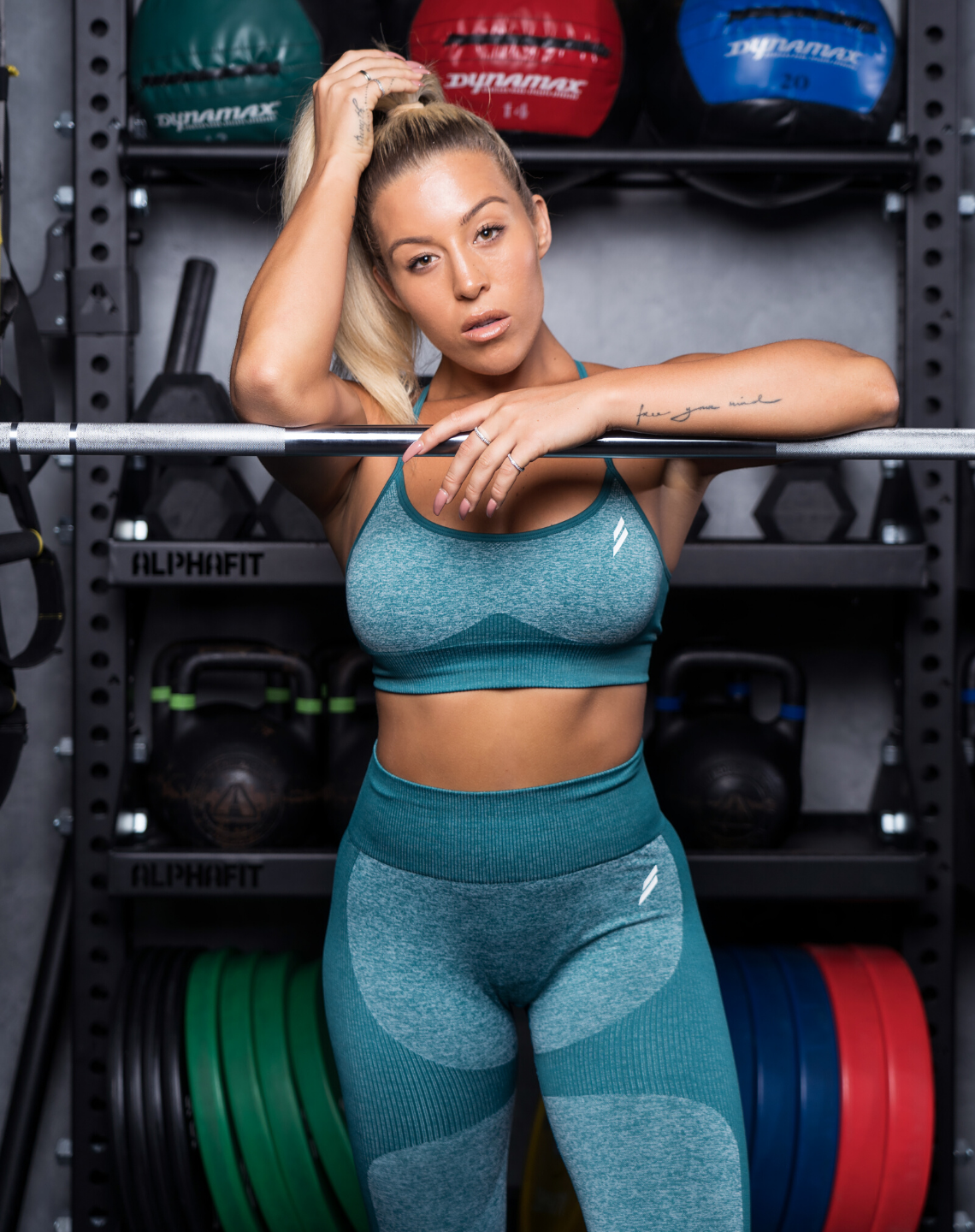 Kali Burns poses in a gym wearing Doyoueven leggings and crop
