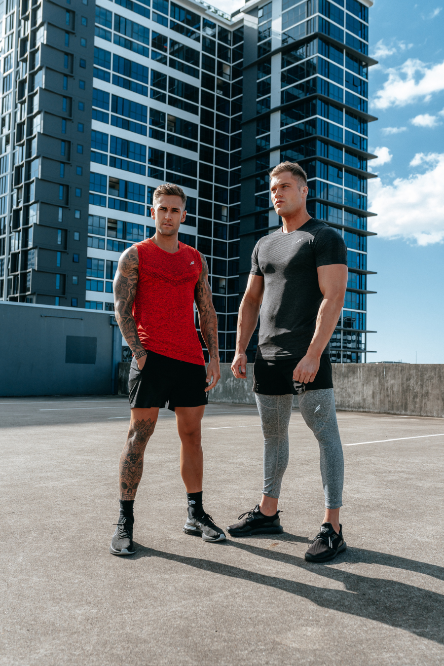 Two male fitness models pose on a city rooftop wearing Doyoueven mens seamless