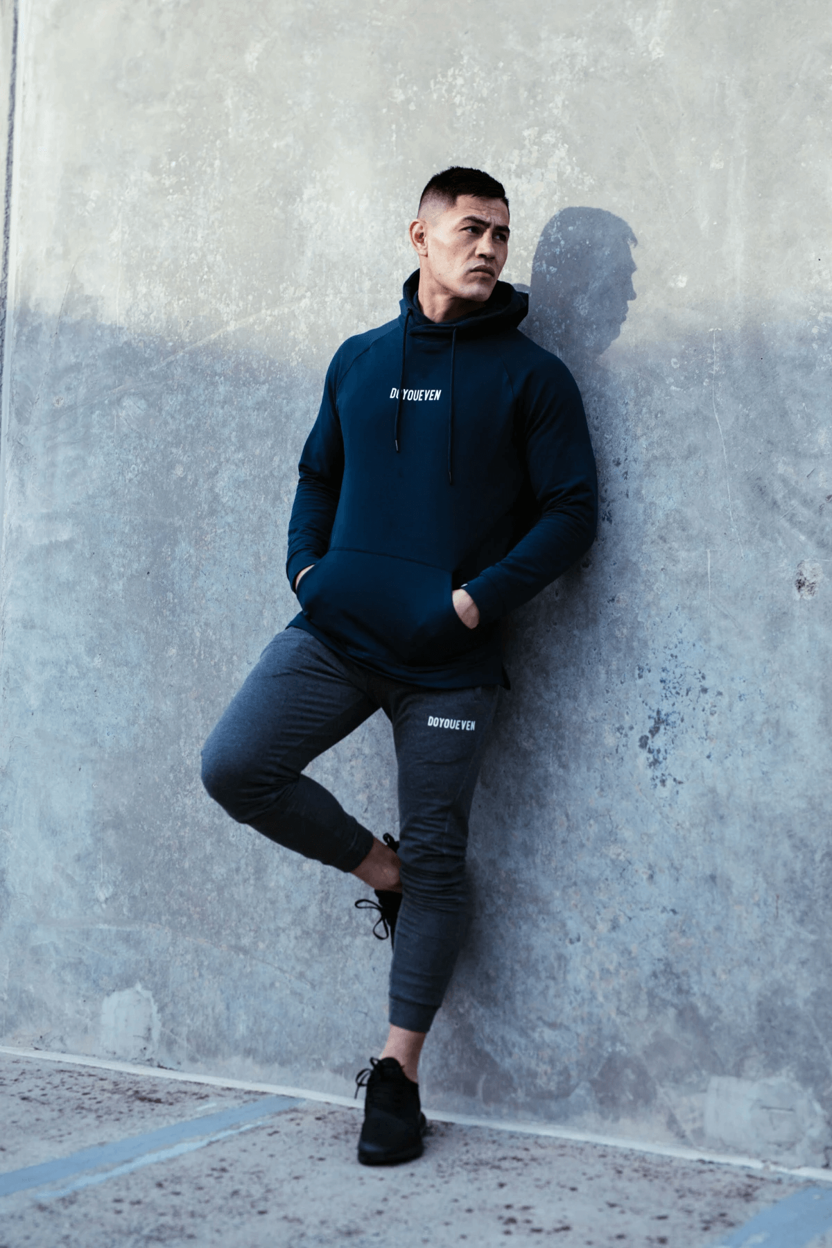 Male Fitness Model poses against a concrete wall wearing Doyoueven Activewear