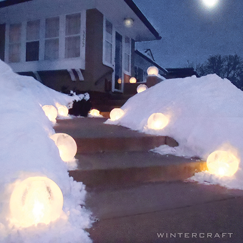 Wintercraft IceLantern  Front entry way lined with candle-lit spherical ice lanterns