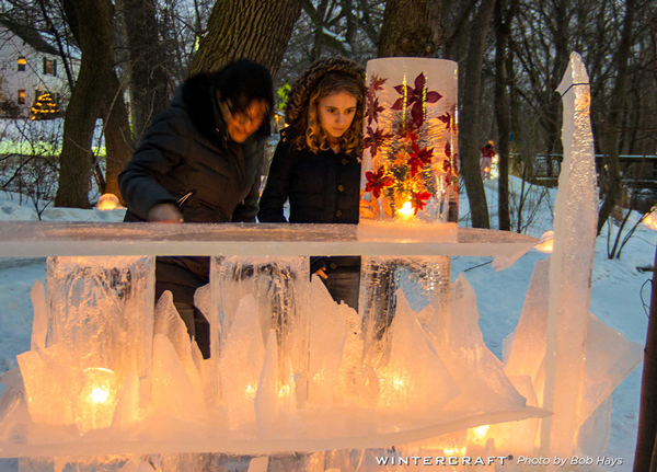 Young woman looking at Leaf Flower Tower on ice bar at the 2018 Middlemoon Creekwalk Wintercraft Ice Wrangler