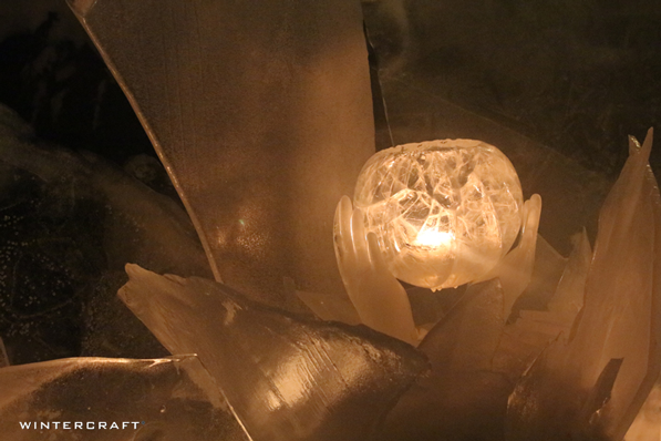 Ice hands hold a candlelit globe in an ice glass display at a Middlemoon Creekwalk