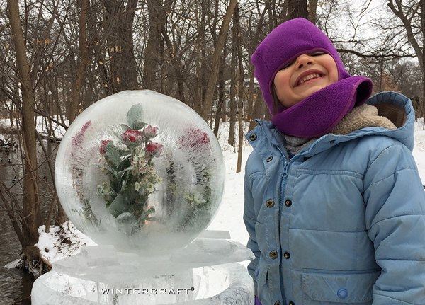 Young helper at the 2018 Middlemoon Creekwalk standing next to a giant globe with flowers inside Wintercraft