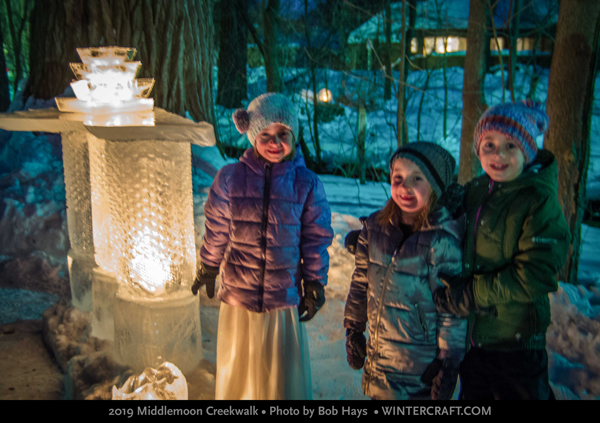 Three kids near the ice bar at Middlemoon Creekwalk 2019 Wintercraft