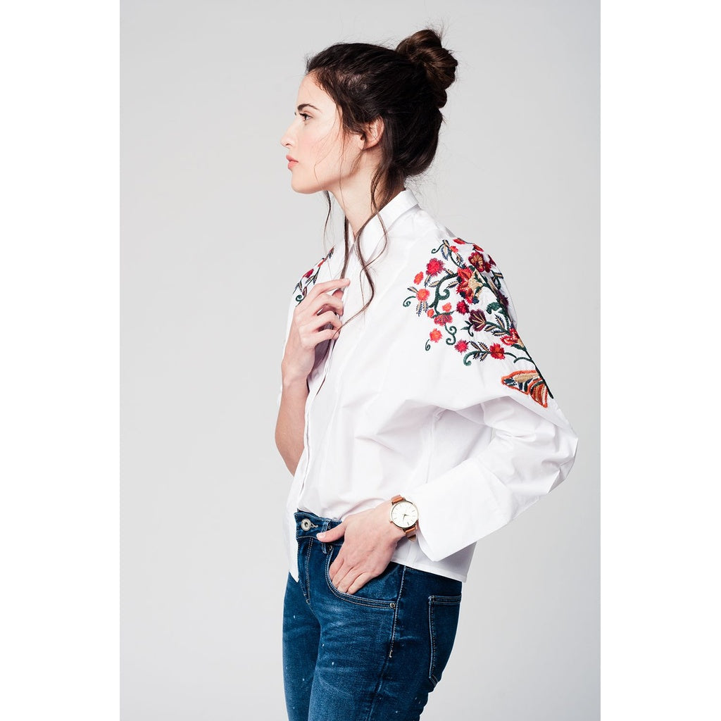 White blouse with flower embroidery detail on the sleeves