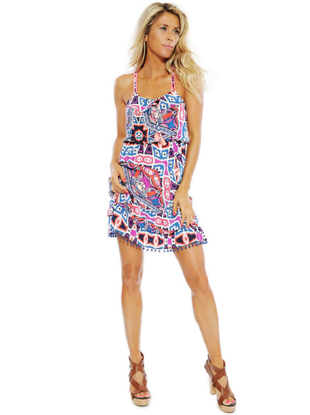 Flowy dress with ruffles on top and skirt and elastic waistline that gives a flexible fit. Decorative pom-pom details on both the top and along hemline.