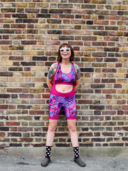 Rouleur Leggings view B - image of woman in brightly coloured bib shorts standing against a brick wall