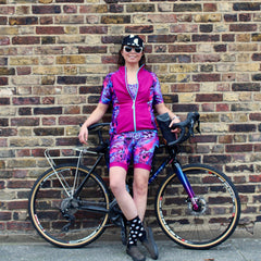 Rouleur Leggings View B - image of woman in brightly coloured cycling shorts and jersey standing in front of a bicycle and a brick wall