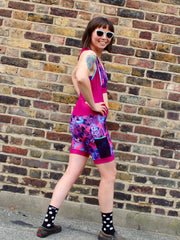 Rouleur Leggings View B - image of woman in brightly coloured bib shorts turning around with hands on hips in front of a brick wall