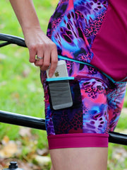 Rouleur Leggings View B - closeup image of brightly coloured shorts and a phone emerging from a mesh pocket on the side of the thigh