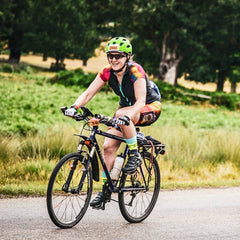 Rouleur Leggings View B - woman on a bicycle wearing ranbow shorts, jersey, and helmet against a grass background