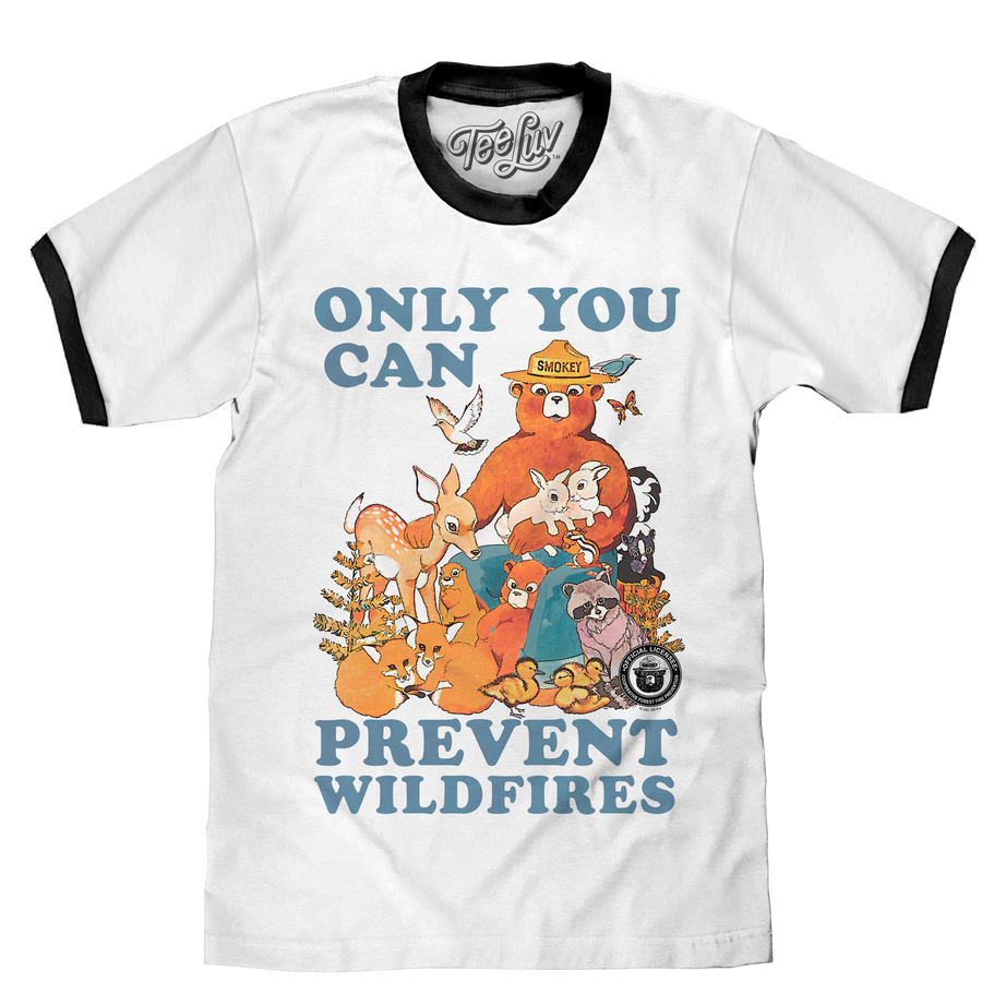 Watercolor graphic of Smokey Bear surrounded by forest animals and the 'Only You Can Prevent Wildfires' text printed on a white ringer tee with black collar and sleeve ribbing.