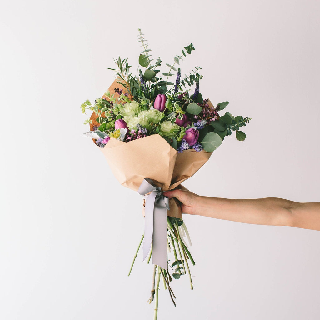 Wildflora Los Angeles florist Ventura Blvd Studio City flower bouquet floral arrangement wedding event special occasion shop store Eucalyptus green foliage variegated pale green light rose fuchsia tulip hyacinth dusty miller veronica purple lilac wrapped brown paper grey gray ribbon hand holding