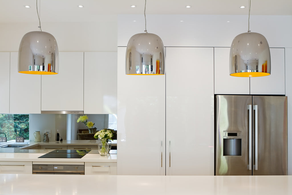 Metallic pendant lights hung in a row over the kitchen bench
