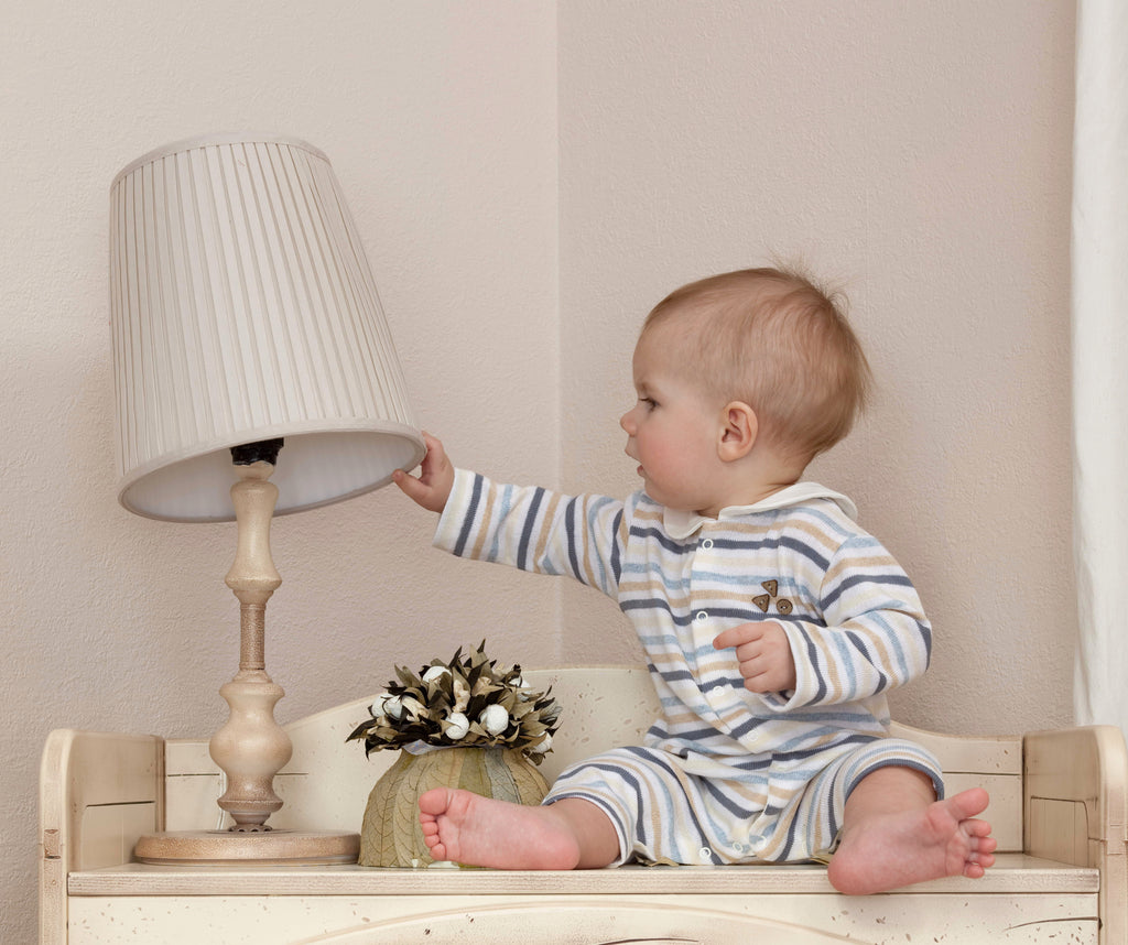 Baby playing with table lamp