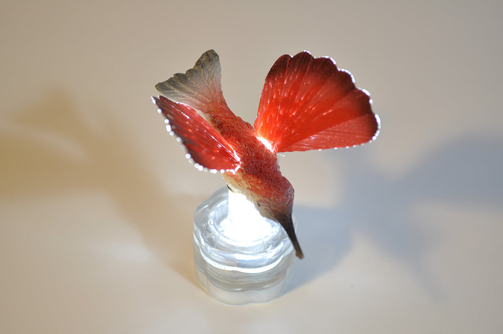 RED SPARKLE LITES FIBER OPTIC HUMMINGBIRD Sparkle Lites Hummingbirds are available in the following colors. Green - Orange - Purple & Red. The Bumble Bee comes in yellow.  Any Hummingbird fits onto any Sparkle Lites base & stem. They light up by placing them on the Sparkle Lites base. The base & stem are sold separately & have replaceable batteries. Placed above floral arrangements or centerpieces, they appear to hover above the flowers, elegant and beautiful & a great talking point in any decor piece.