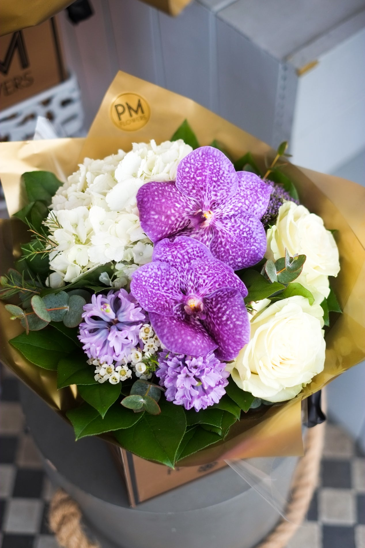 A cute & short bouquet featuring white hydrangea, lilac vanda, white roses, lilac hyacinth, spray roses, and a mixture of foliages.
