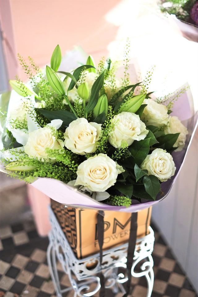 This white flower bouquet containing large headed white roses, fresh white lilys and foliages.