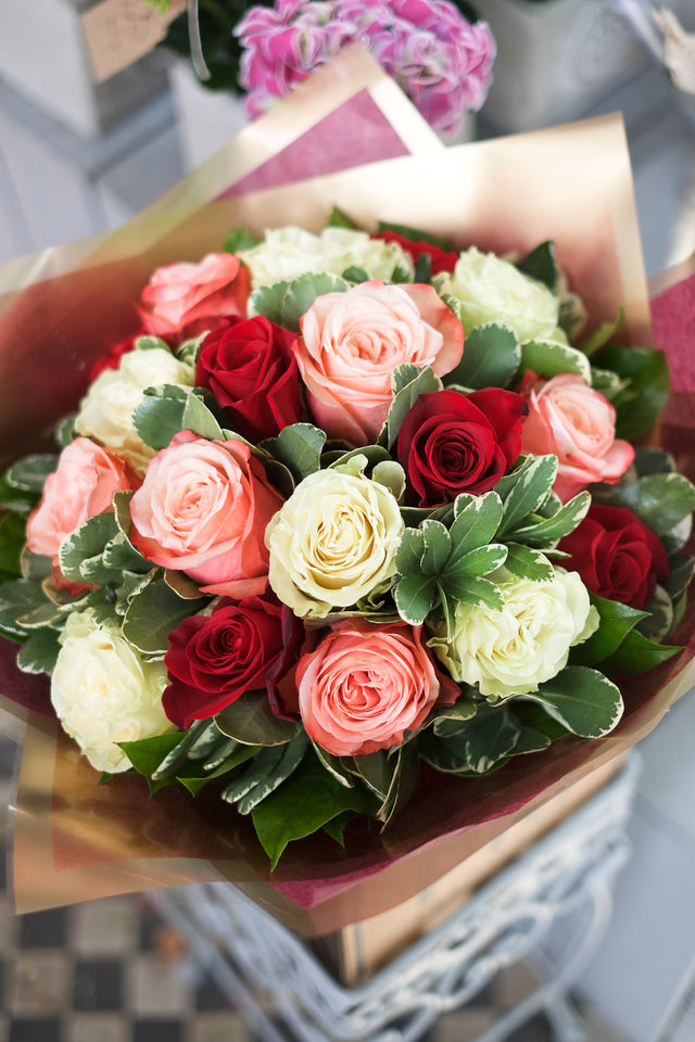 A Flower mixed rose bouquet consisting of red, white and coffee coloured roses combined with pittosporum foliage
