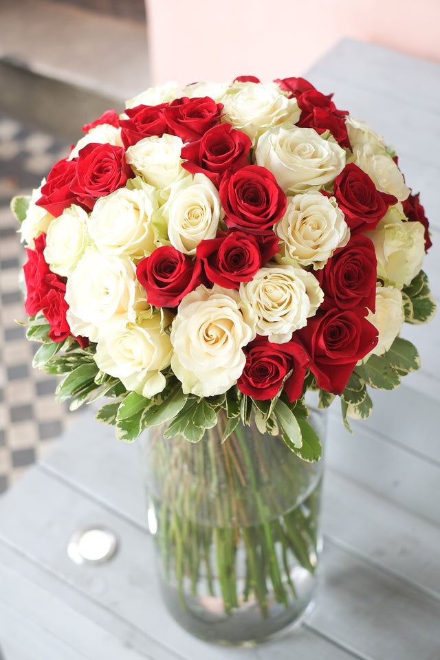 Innocent Beauty flower bouquet exudes romantic and elegant tones. It features 50 long stemmed and large headed white and red roses with outer foliage.