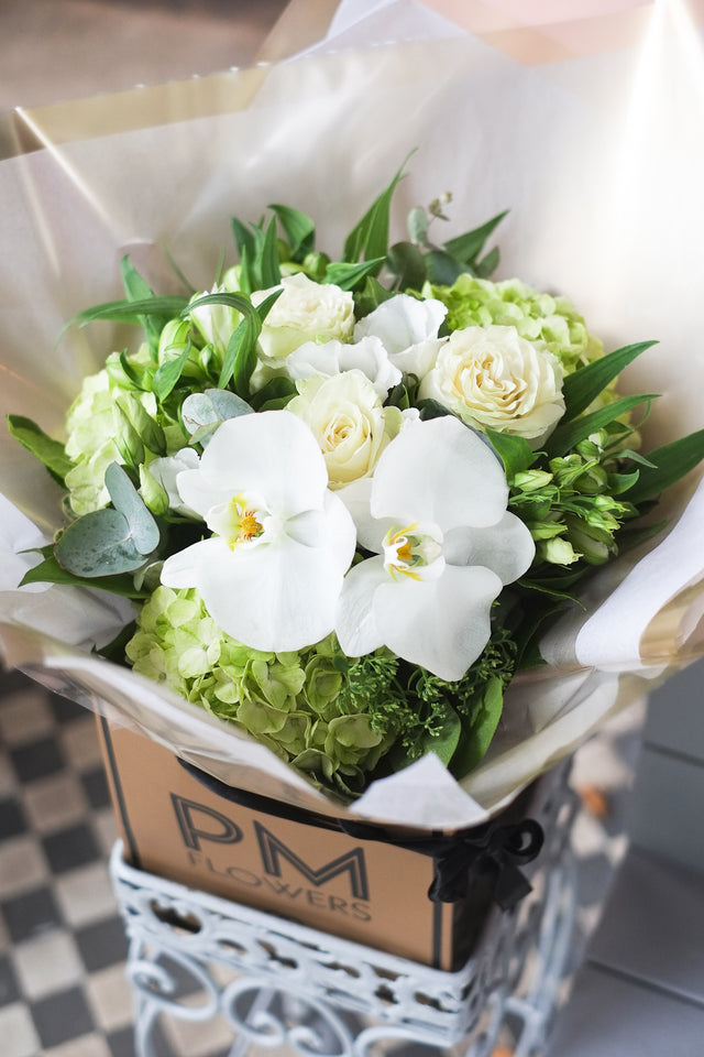 A elegant flower bouquet of green hydrangeas, white roses, white lisianthus and white alstomera. Enough to make you smile on a cloudy day.