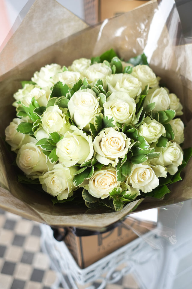Bouquet of luxurious assortment of large headed white roses and pittosporum foliage