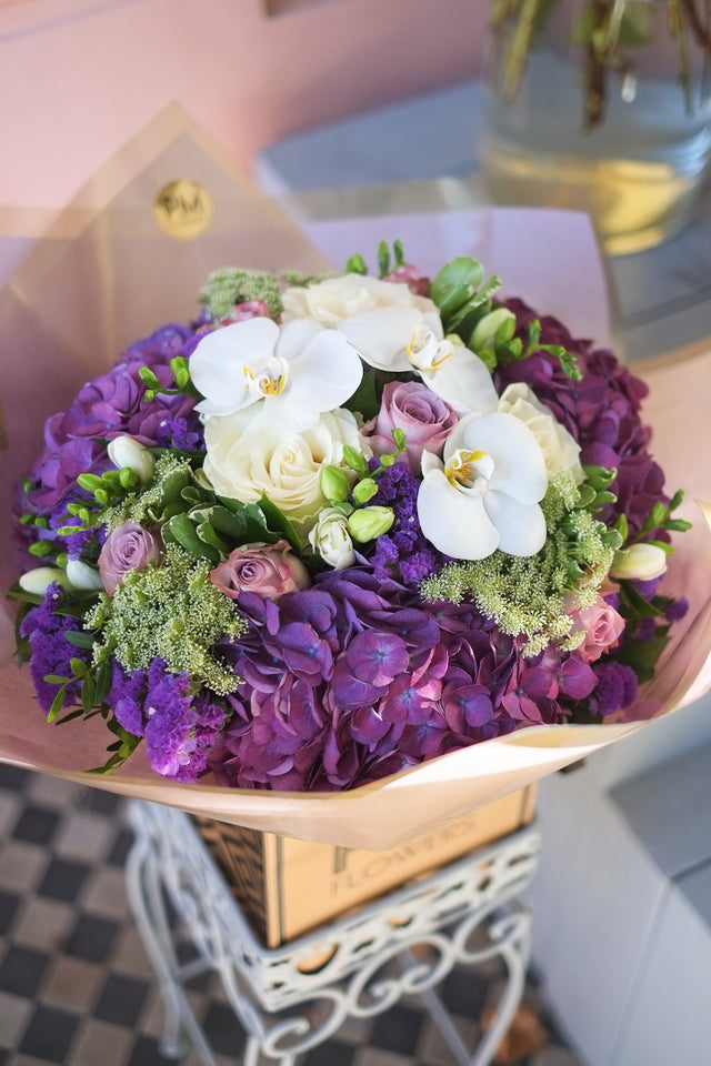 Big purple hydrangeas, large white headed roses, lilac roses, scented freesias, statice, white phalaenopsis. Another wondeful bouquet in london