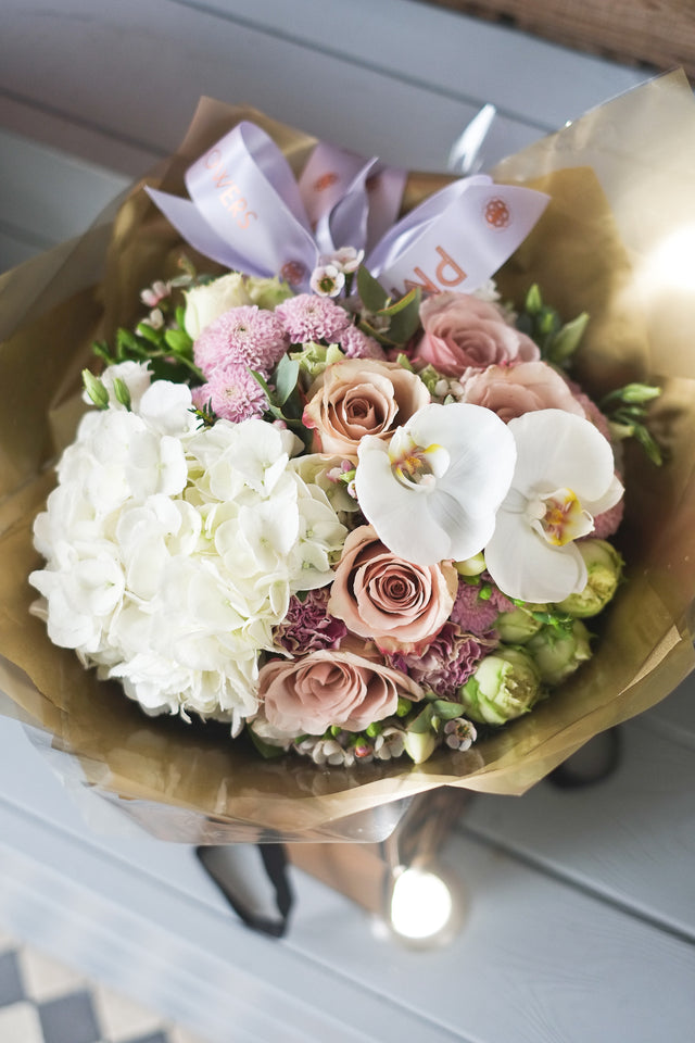 Prewett Miller Bouquet has an romantic mix of sandy cream roses, spray roses, white hydrangea and white phalenopsis. Stunning floral arrangement . Best seller