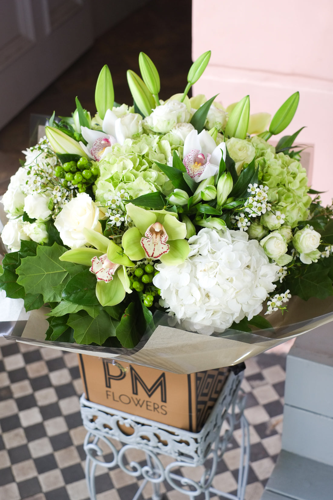 An enchanting flower bouquet featuring spray and large headed white roses, white and green hydrangeas, cymbidium, white lilies, waxflower and foliage.