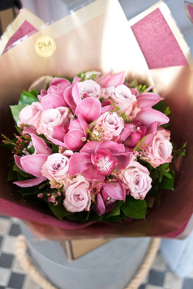 Flower bouquet of soft pink roses accompanied with pink cymbidiums - a strikingly elegant bouquet in London.