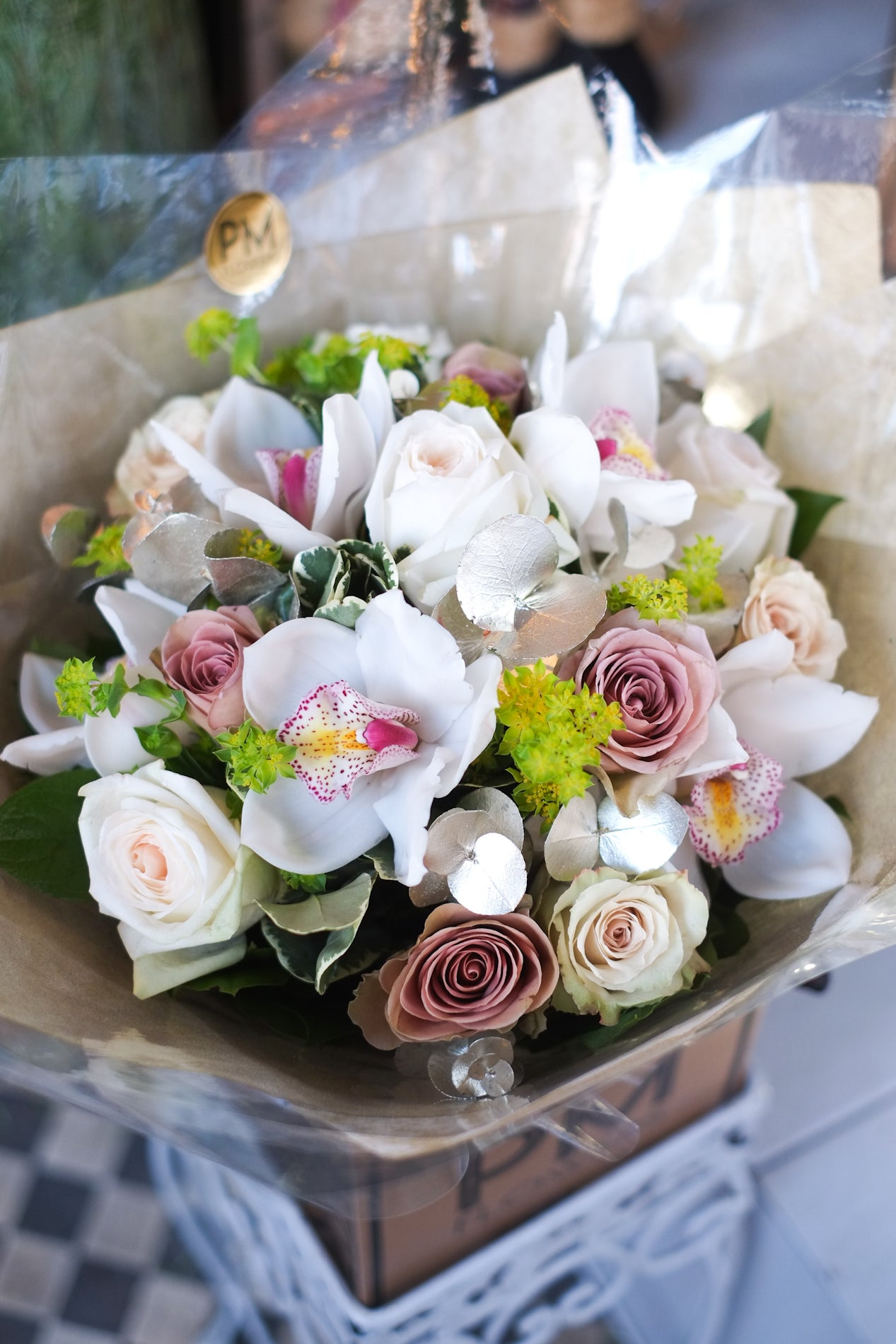 Sweet fragrance and rich textures is what this flower bouquet exudes. A combination of premium scented garden roses balanced with antique lilac roses with accents of silver, beige and greens.