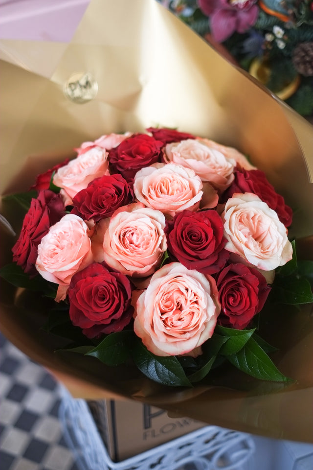 premium flower bouquet of red roses with an exquisite champagne-cream-powder-peach rose