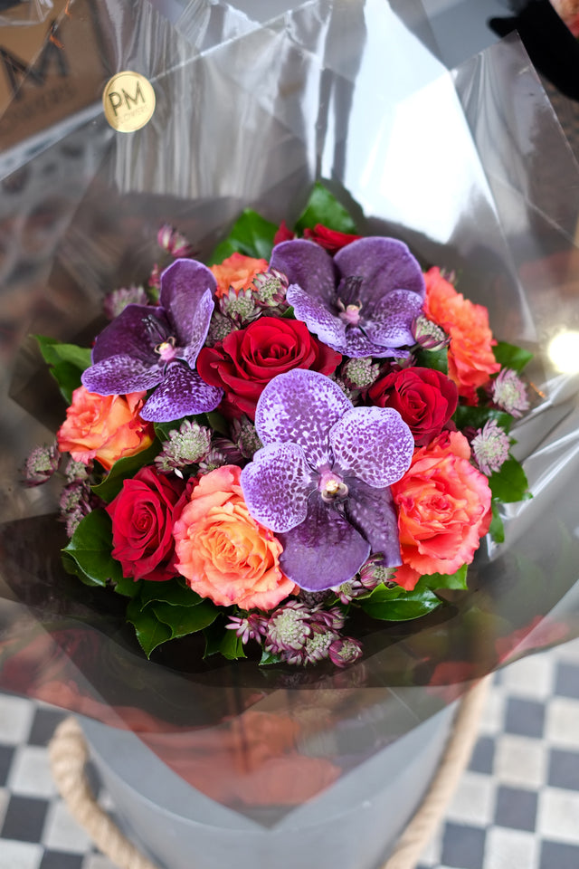 A flower bouquet of orange and red roses paired with large aubergine vanda heads. PM flower in London
