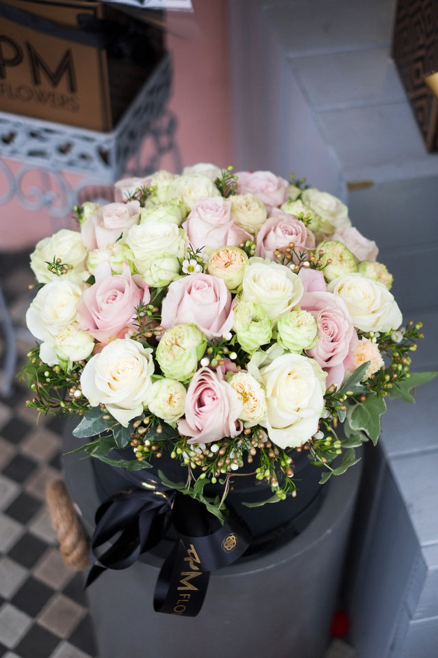 The Pure elegance Hat Box features a mix of white and soft pink large headed roses, spray garden roses and a hint of foliage.