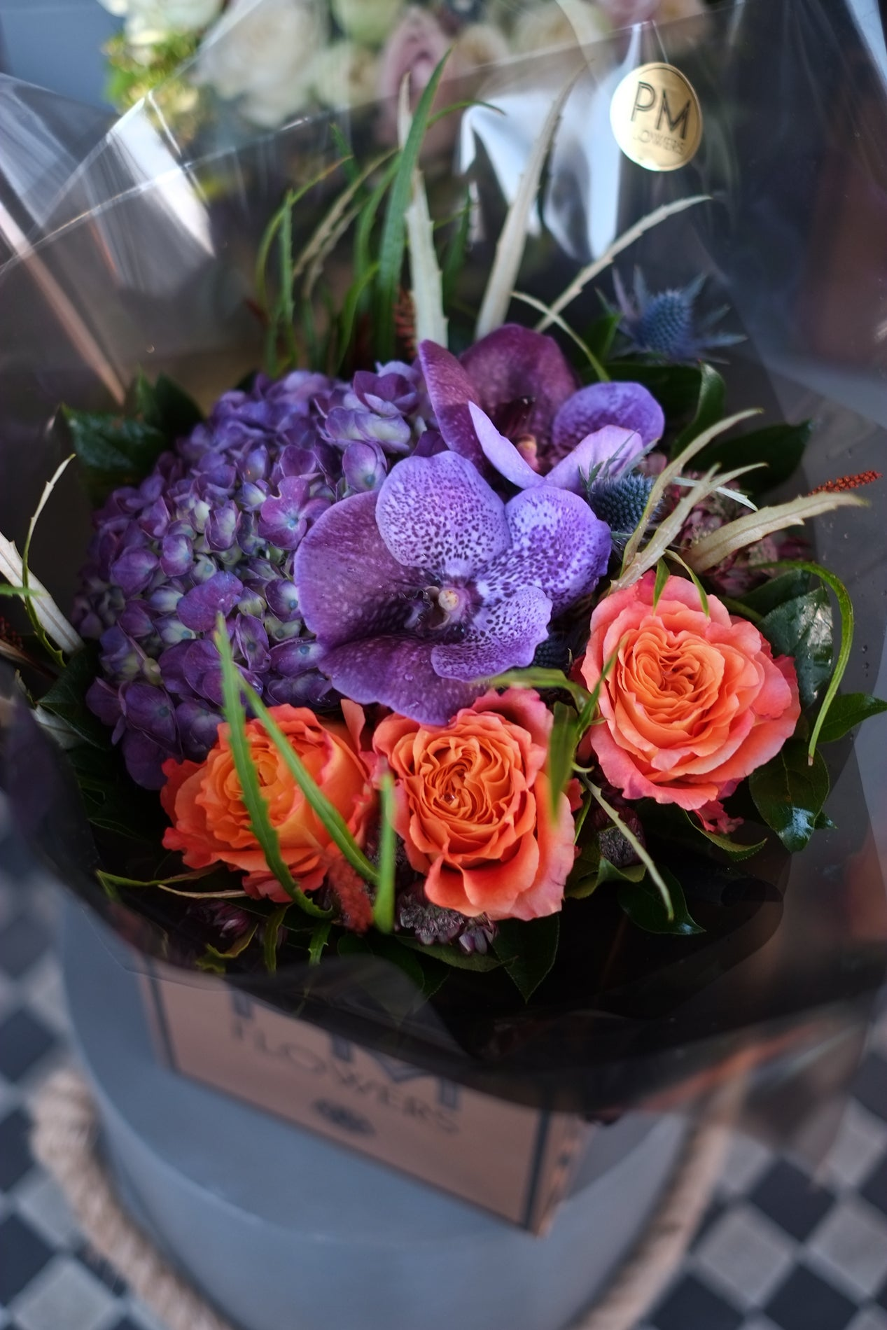 A London flower arrangement of purple hydrangea, vanda and large orange roses accompanied with some light wil foliage.