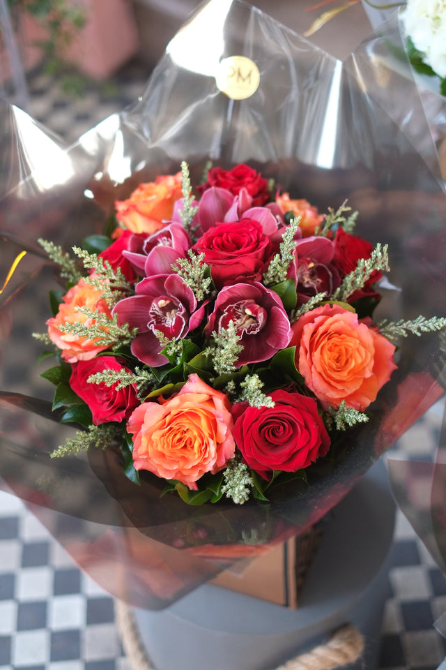 Flower Bouquet of luscious red and orange roses infused with cymbidium orchids and feathery foliage.