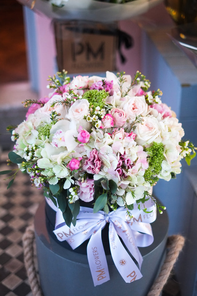 The Sweet Scented Hat Box is a breathtaking arrangement with premium scented garden roses, spray roses, large hydrangeas, cymbidium orchid heads, lisianthus