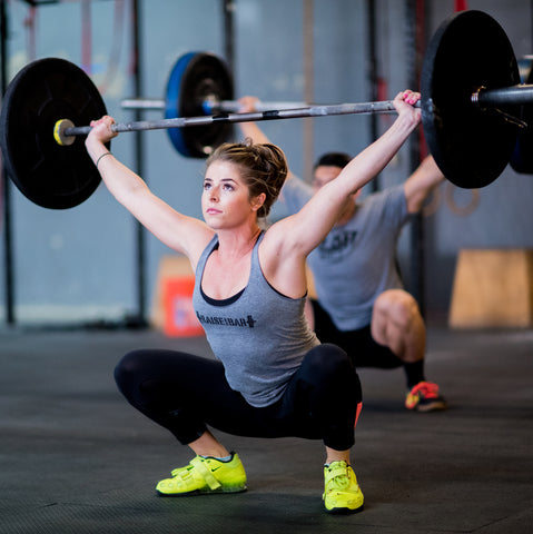 Woman wearing weightlifting apperal and lifting heavy weights.