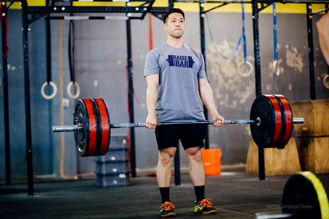 Man lifting weights with a weightlifting t-shirt on.