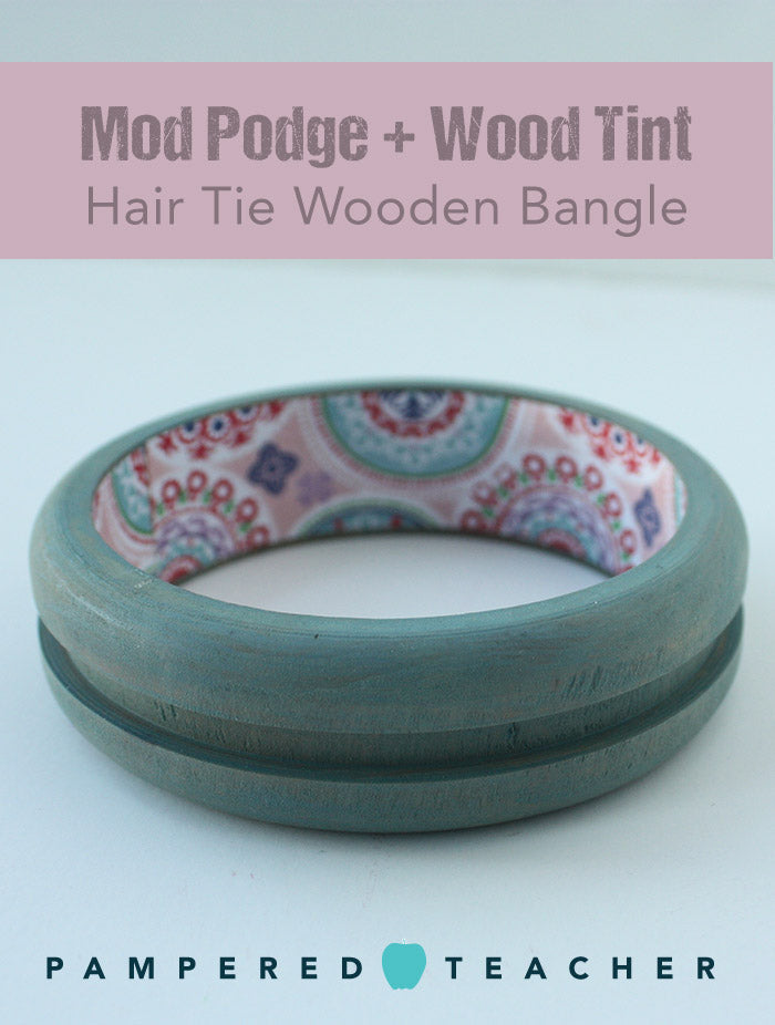 wood bangle decorated with Mod Podge, scrapbook paper and Folk Art blue wood tint. A fun and whimsical way to wear a hair tie at work
