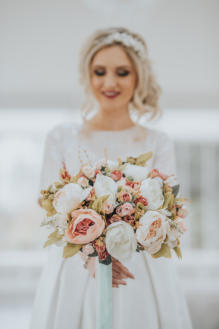 Bride holding a bouquet of flowers. Photo by Karol Makula
