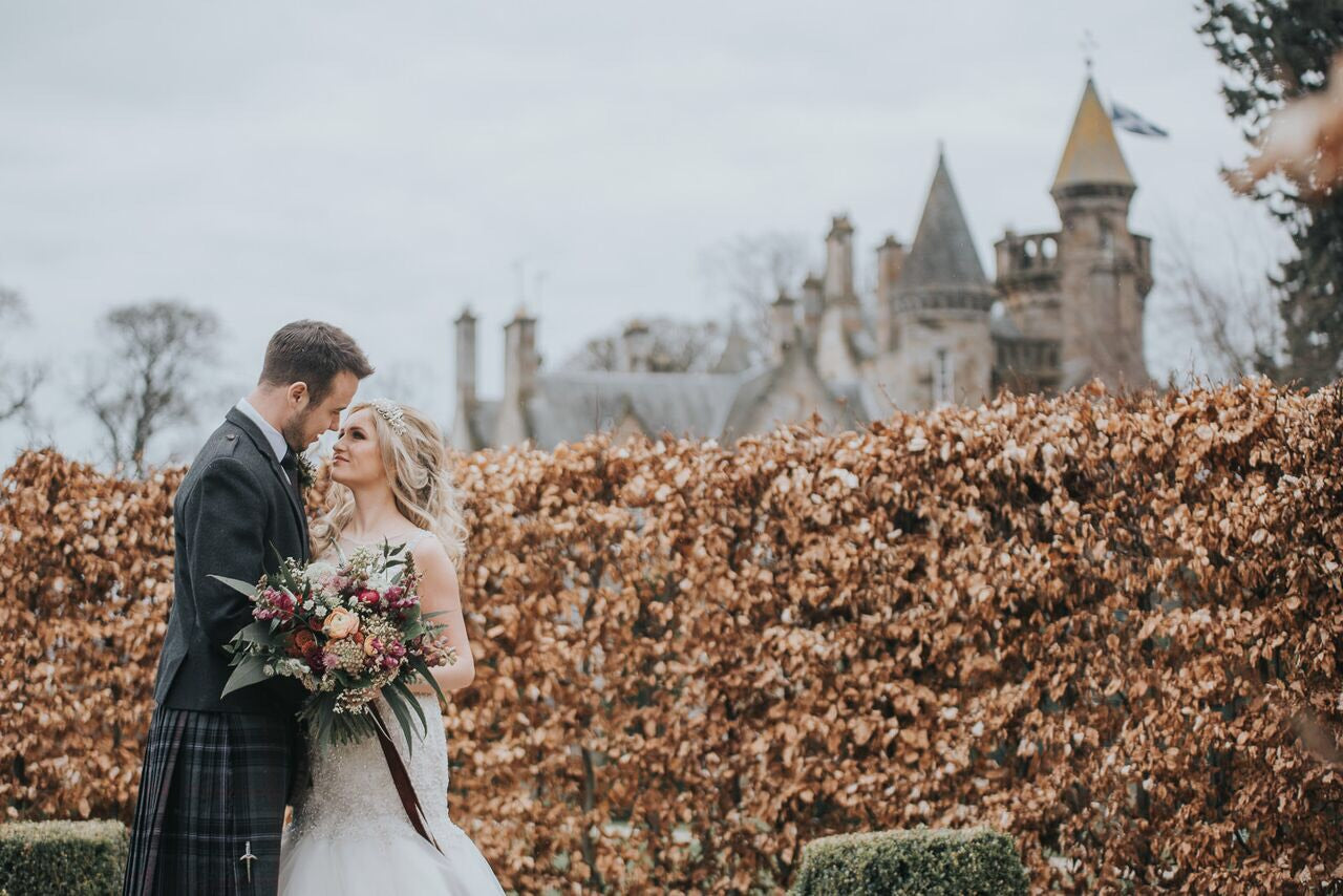 Married couple standing in front of a castle. Photo by Karol Makula