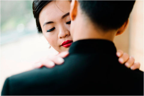 Image of a woman with a bright red lip holding the shoulders of a man in a suit