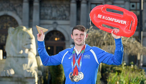 Olympian and Commonwealth Champion Swimmer Ross Murdoch holding up a floatation device and a sandwich