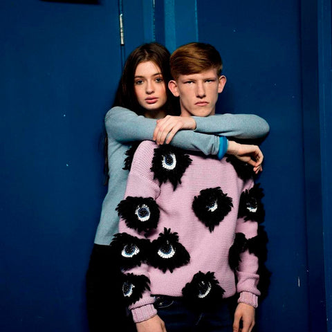 Female model stands with her arms around a male model in front of a blue background
